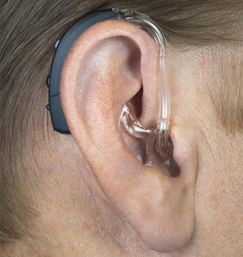 Interton Gain hearing aid on man's ear.