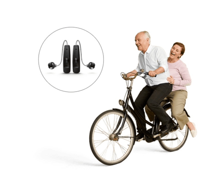Couple wearing Interton affordable hearing aids and riding a motorbike.