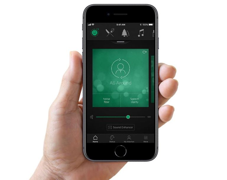 Hand holding an iPhone with the hearing aid app Interton Sound,