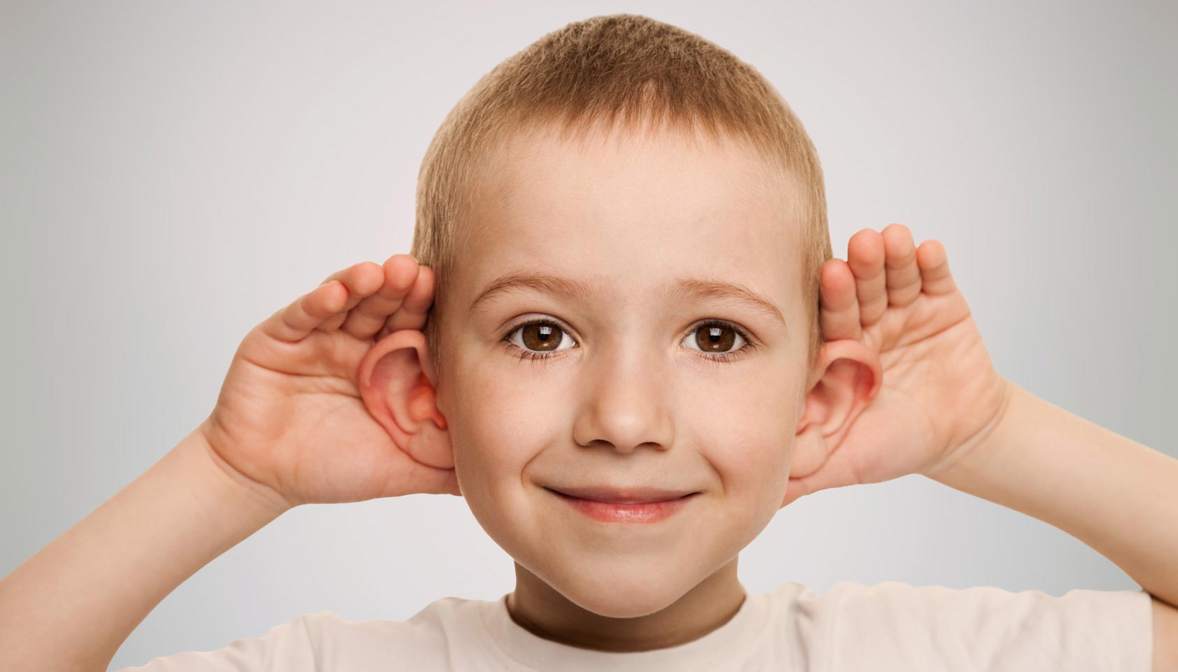 Boy grabbing his ears and smillling - everything you need to know about hearing loss.